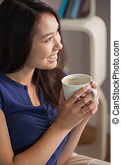 Happy asian woman sitting on the couch holding mug of coffee looking away in sitting room at home