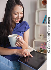Happy asian woman sitting on the couch holding mug of coffee using tablet pc in sitting room at home