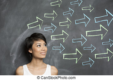 Happy Asian woman standing in front of a dark chalkboard with arrow signs drawn pointing.