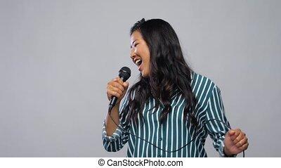 happy asian woman with microphone singing karaoke - leisure ...