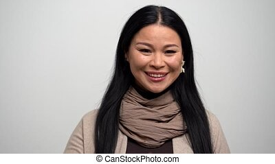 Happy Asian Woman with Narrow Eyes on a White Background.