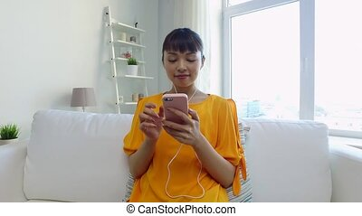 happy asian woman with smartphone and earphones - people,...