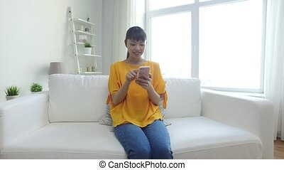 happy asian woman with smartphone at home