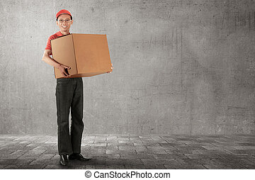 Happy asian young courier carrying a cardboard box