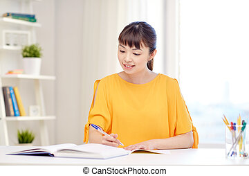 happy asian young woman student learning at home - people,...