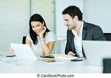 Happy atmosphere between a businesswoman and a businessman in an office