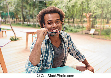 Happy attractive african young man in glasses sitting outdoors