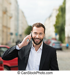 Happy attractive businessman on his mobile phone