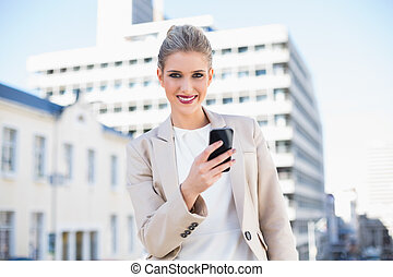 Happy attractive businesswoman sending a text message