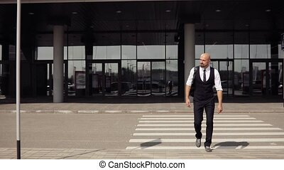 Happy attractive caucasian businessman walking outside near big office building and looking around.