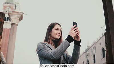 Happy attractive Caucasian female tourist taking smartphone photos of ancient buildings in old town of Venice Italy.