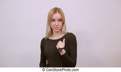 Young Blonde Woman In Black Sweater With Stylish Watch On White Background, Happy Attractive Girl Smiling Points forefinger At The Person In Front. Concept Of Guilty People And Charges