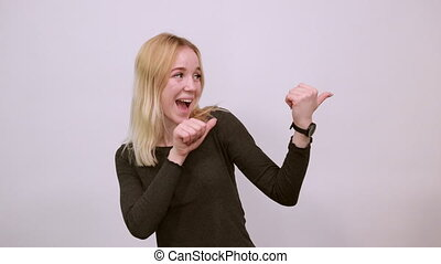 Young Blonde Woman In Black Sweater With Stylish Watch On White Background, Happy Attractive Girl Smiling Points Thumbs At The Person behind. Concept Of Guilty People And Charges