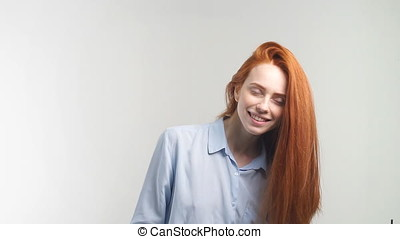 Happy attractive girl with curly red hair smiling looking at camera. Slow motion.