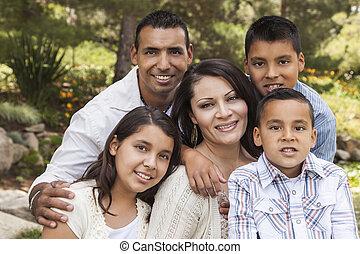 Happy Attractive Hispanic Family Portrait In the Park