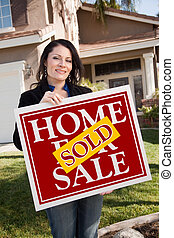 Happy Attractive Hispanic Woman Holding Red Sold Home For Sale Sign In Front of House.