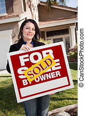 Happy Attractive Hispanic Woman Holding Sold For Sale By Owner Real Estate Sign In Front of House