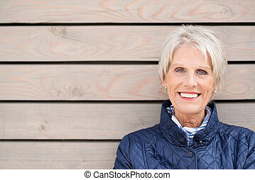 Happy attractive senior lady standing against wood