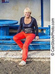 happy attractive senior woman at an old abandoned busstop