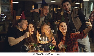 Happy attractive students in birthday party hats are...