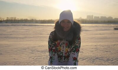 Happy attractive woman having fun and throwing the snow in winter field on sunset city background in slow motion with lense flare effects. 1920x1080