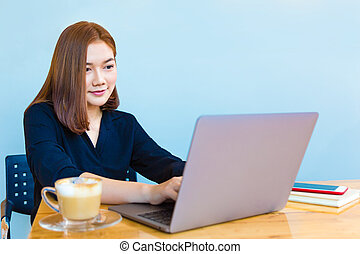 Happy attractive young Asian businesswoman working on her...