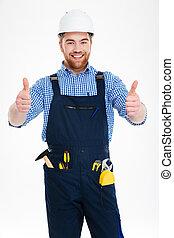 Happy attractive young builser in helmet showing thumbs up