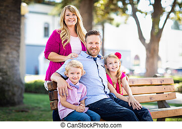 Happy Attractive Young Caucasian Family Portrait in the Park