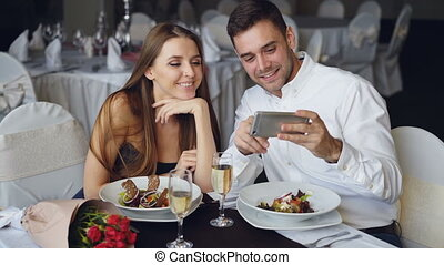 Happy attractive young people are watching smartphone together, smiling and talking while having dinner in restaurant. Modern technologies and romance concept.