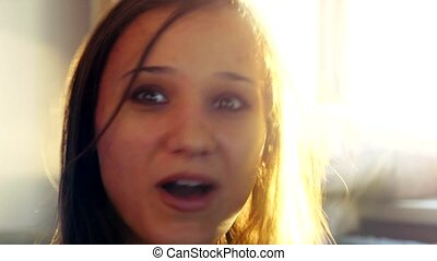 Happy attractive young woman having a video chat in sunny room at sunset time with lens flare. 4k
