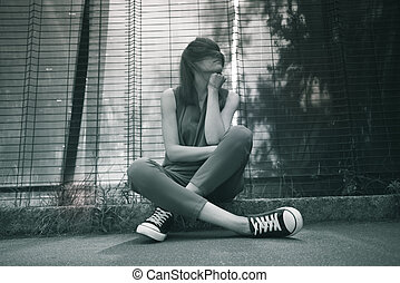 Happy attractive young woman in  sitting on city street