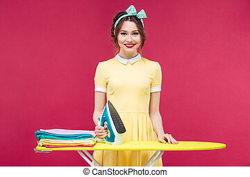 Happy attractive young woman standing and ironing clothes ...