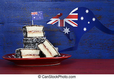 Happy Australia Day January 26 party food with iconic Australian lamington cakes on dark red and blue vintage rustic recycled wood background.