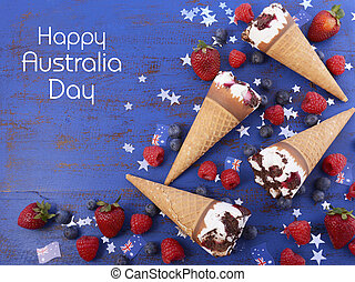 Happy Australia Day party ice cream cones with berry fruit and flags on a blue wood background, overhead with copy space.