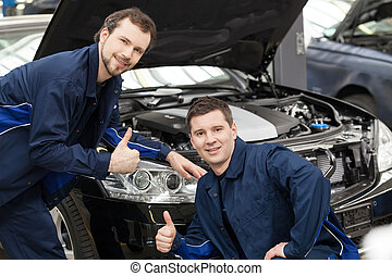 Happy auto mechanics. Cheerful young mechanics gesturing while standing in front of the car and smiling at camera