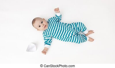 Happy baby and paper boat - Baby wearing striped romper and...
