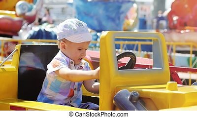 Happy baby boy drives on yellow toy car in the attraction park on sunny summer day in slow motion. 1920x1080