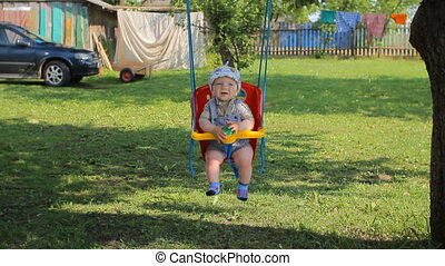 Happy baby boy having fun on a swing ride at a playground a summer day. Baby less than a year
