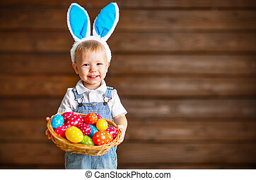 Happy baby boy in Easter bunny suit with basket of eggs