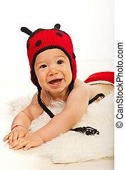 Happy baby boy in ladybug hat