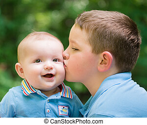 Happy baby boy kissed by brother