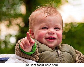 Happy baby boy laughing with joy and pointing at you