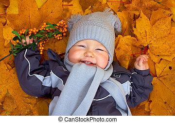 happy baby boy lies among fallen leaves