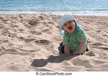 Happy baby boy on the beach