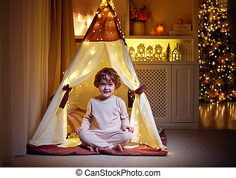 happy baby boy playing in illuminated teepee tent at home on Christmas holidays
