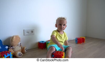 Happy baby boy playing with colorful blocks at home. Gimbal motion