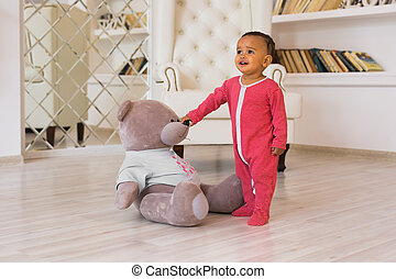 Happy baby boy playing with his teddy bear