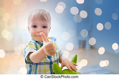 happy baby boy playing with toy showing thumbs up
