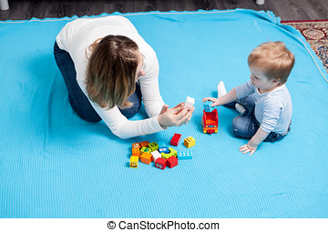 Happy baby boy playing with toys next to her mother