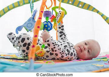 Happy baby boy smiling on playmat - Happy newborn lies on...